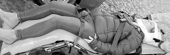 Kvinna som ligger på en bår